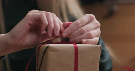 karácsonyi ajándék : Closeup of young female hands making red ribbon bow on craft paper gift box