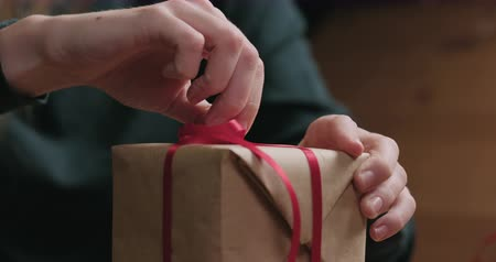karácsonyi ajándék : Slow motion closeup shot of young female hands unties red ribbon bow on craft paper gift box