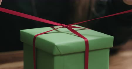 луки : Slow motion closeup shot of young female hands unties red ribbon bow on green paper gift box Стоковые видеозаписи