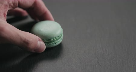 menta : Slow motion closeup man hand put light blue macaron on slate board Stock mozgókép