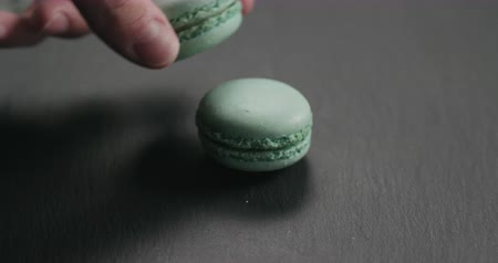 candy : Slow motion closeup man hand put light blue macarons on slate board