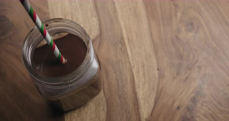 dark green : Slow motion drinking cocoa with christmas striped paper straw from glass jar on wood background with copy space shot from above Stock Footage