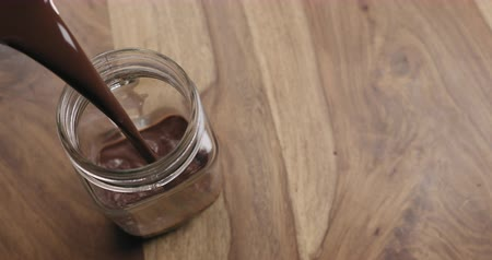 zab : Slow motion pour hot cocoa in glass jar on wood background with copy space