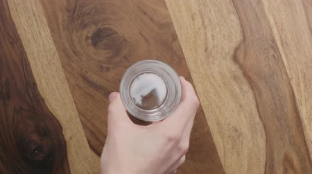 oldódó : Slow motion man hand bring empty glass with dissolved effervescent tablet to wood table top view Stock mozgókép