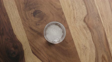 oldódó : Slow motion man hand drop effervescent tablet in glass of water on wood table top view
