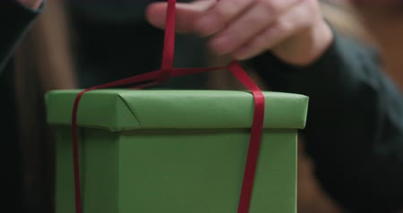 луки : Closeup of young female hands making red ribbon bow on green paper gift box