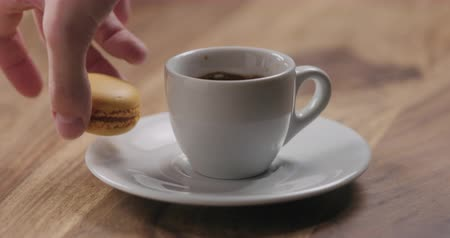 fincan tabağı : Slow motion man hand put orange macaron on saucer with coffee cup