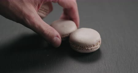 arduvaz : Slow motion closeup man hand put beige macarons on slate board Stok Video