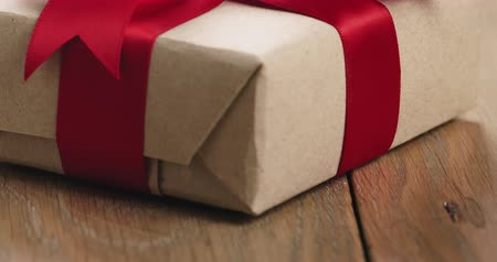 karácsonyi ajándék : Closeup pan of brown paper gift box with red ribbon bow on oak table