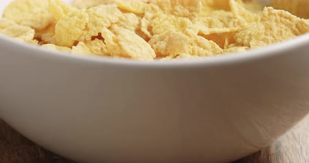 corn flakes : Closeup pan of dry corn flakes in white bowl on wood table