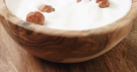 pan shot : Closeup pan of homemade yogurt with hazelnuts in wood bowl on wooden table