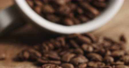 inverted : Closeup pan of overturned cappuccino cup with roasted coffee beans on wood table