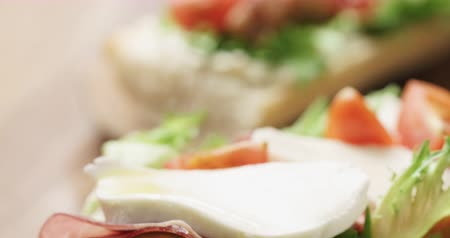 olive wood : Closeup pan of open sandwich with prosciutto, mozzarella and tomatoes on kitchen table Stock Footage