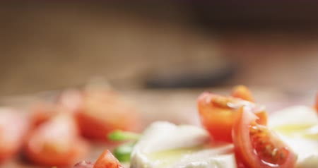 プロシュート : Closeup pan of open sandwich with prosciutto, mozzarella and tomatoes on kitchen table 動画素材