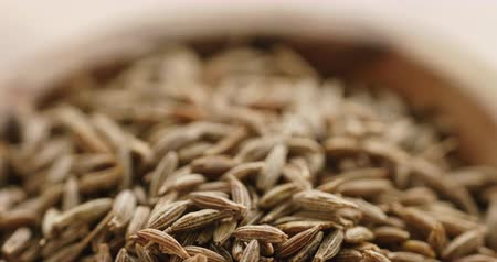 pan shot : Closeup pan of cumin zira seeds in wood bowl on table