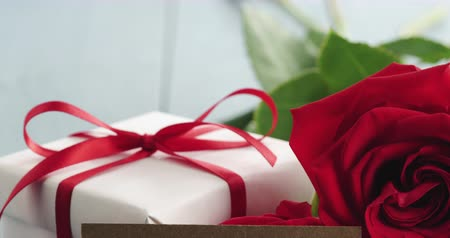 я тебя люблю : Closeup pan of three red roses on blue wood table with gift and i love you paper card Стоковые видеозаписи