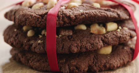 engorda : Closeup pan of stack of homemade chocolate cookies with hazelnuts tied with ribbon on wood table
