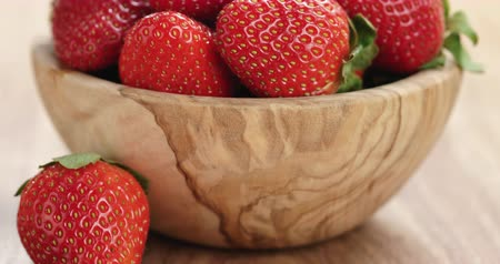 picked : Closeup pan of fresh strawberries in bowl on wood table