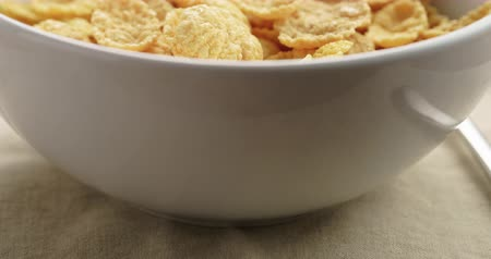 corn flakes : Closeup pan of dry corn flakes for breakfast in bowl on table Stock Footage