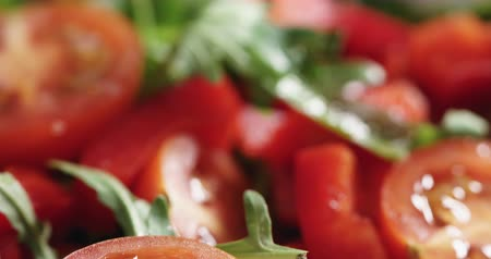 olive wood : Closeup pan of cherry tomatoes with arugula salad in white bowl Stock Footage