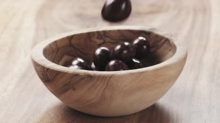 dragee : Slow motion of almonds covered with chocolate fall in wood bowl on wooden table Stock Footage