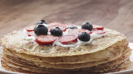 desszertek : Slow motion of sprinkling sugar powder on blinis or crepes with fresh berries