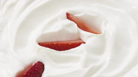 çırpılmış : Slow motion of sliced strawberry falling into cream