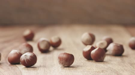 gedroogde vruchten : unpeeleed hazelnuts falling on wood table in slow motion