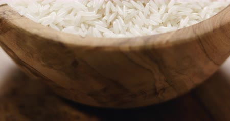 basmati : Closeup pan of dry basmati rice in wood bowl on table
