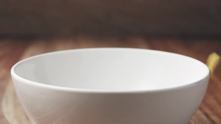 corn flakes : corn flakes falling in white bowl on wooden table in slow motion