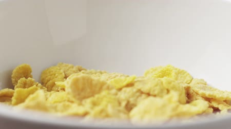 corn flakes : corn flakes in white bowl on wooden table slide back Stock Footage