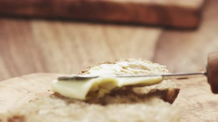 espalhando : Slow motion of female teen hand spreads butter on slice of rustic bread Stock Footage