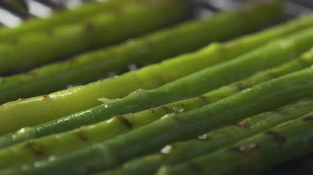 kuşkonmaz : Slide slow motion shot of cooking frozen green asparagus on grill pan