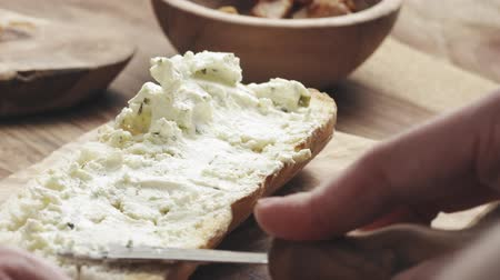 bagietka : man spread cream cheese with herbs over baguette in slow motion