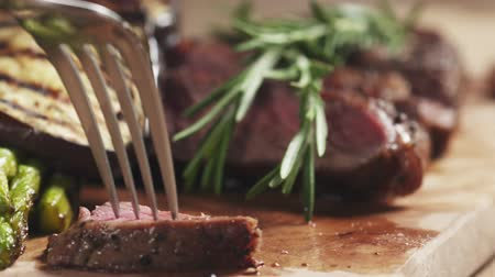 villa : slow motion slide shot of taking piece of rib eye steak with fork