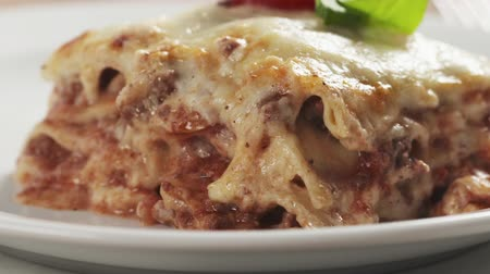 camadas : Slide shot of homemade lasagna portion on white plate on wood table Stock Footage
