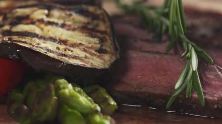 főtt : Slide slow motion shot of serving medium rib eye steak with rosemary Stock mozgókép