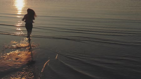 backwards : Aerial forward fly over teen girl barefoot running into water on baltic sea beach and raising arms in sunset time Stock Footage