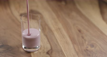 turmix : Slow motion pouring blueberry yogurt into the glass on wood table, 60fps Stock mozgókép