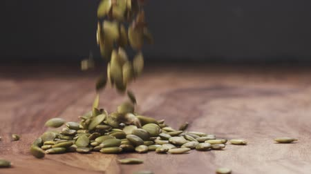 soyulmuş : Slow motion pumpkin seeds falling on wood table