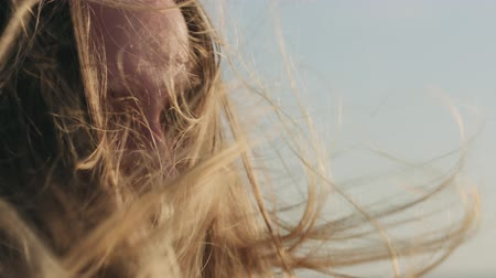 explodindo : Slow motion closeup portrait of young girl standing on a beach and wind blows her hair