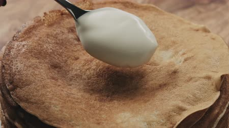tejföl : Slow motion adding sour cream on top of pancakes or blini