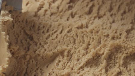 pralina : Slow motion closeup hazelnut praline ice cream scooping with spoon