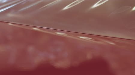 detailing : Slow motion handheld closeup peeling off protective film from a car Stock Footage
