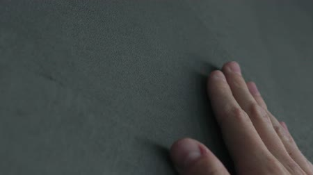 anyagi : Slow motion man hand touches decorative concrete finish