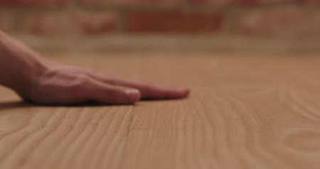осмотр : Closeup man hand touches ash wood floor