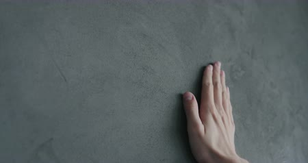 хозяин : Slow motion man hand touches decorative concrete finish