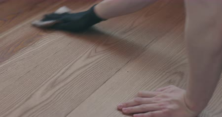 trabalhador manual : Sow motion man applying protective oil finish to ash floor