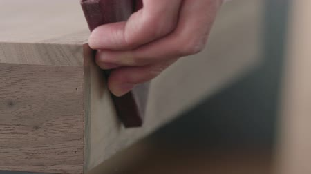 sand paper : Slow motion woodworker hand sanding black walnut drawer tray