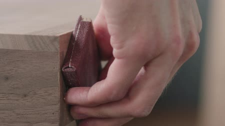 nogueira : Slow motion woodworker hand sanding black walnut drawer tray